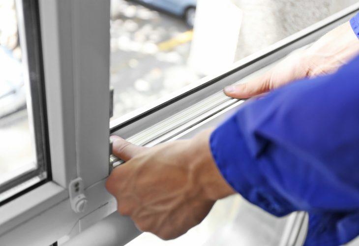 Construction worker putting sealing foam tape on window in house